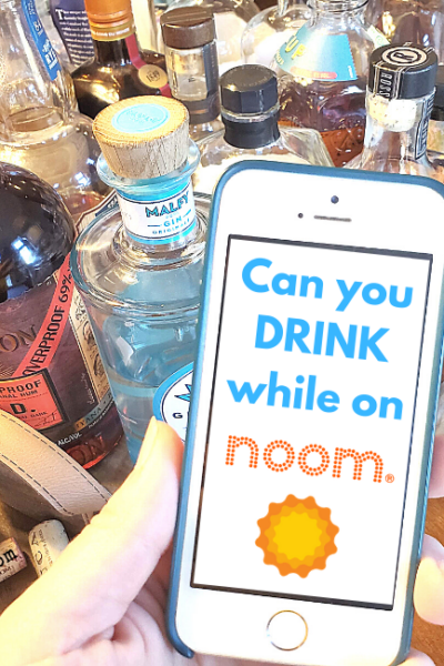 Photo of a hand holding a mobile phone that says Can you Drink While on Noom. Hand is in front of several bottles of alcohol.