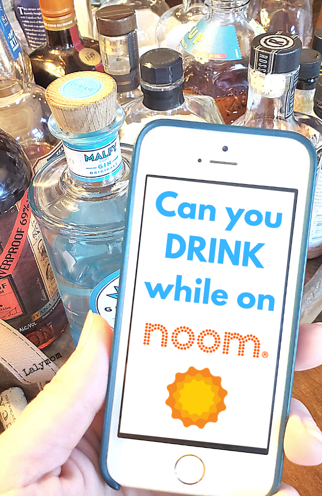"Mobile Phone displaying the question ""Can You Drink While on Noom?"" in front of liquor bottles."