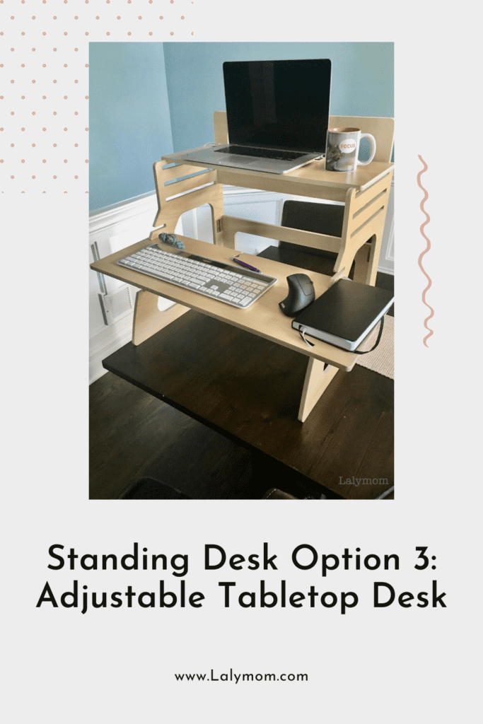 Standing desk option - folding, two shelf, adjustable standing desk, shown with laptop, keyboard and ergonomic mouse.